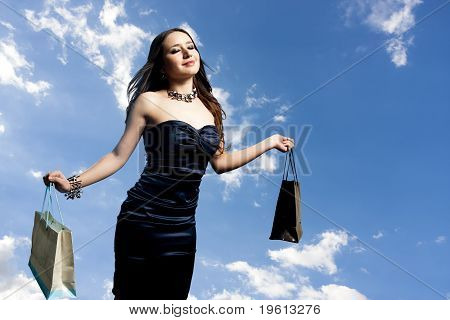 A Beautiful Portrait Of A Young Attractive Woman Holding Shopping Bags.