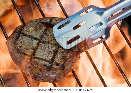 striped steak on fiery grill closeup