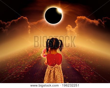 poster of Amazing scientific natural phenomenon. Total solar eclipse glowing above child on pathway with night sky and clouds. Full solar eclipse is photo realistic illustration. Sepia tone.