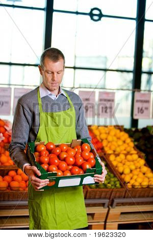 A male grocery owner with a box of ripe tomatoes