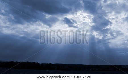 Sun rays in dark blue sky