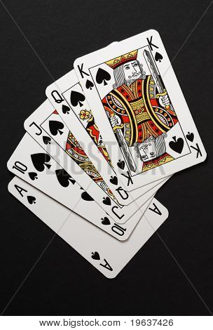 Royal flush poker win combination - closeup of playing cards: king, queen, jack, ten and ace