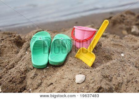 Closeup de zapatillas de niños y juguetes en la playa