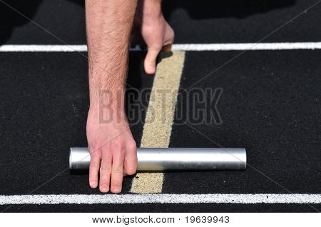 Hand Holding A Baton At The Starting Line