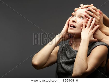 Portrait of a troubled woman restrained by several hands