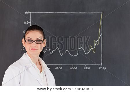 Isolated scientist standing near the blackboard and looking at the camera