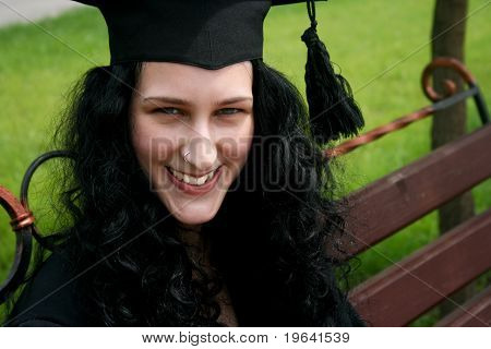 Smiling Caucasian Student Sitting On The Bench