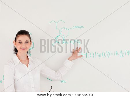 Female scientist looking at the camera while standing in front of a white board