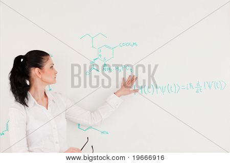 Scientist explaining a formula written on a white board to her students