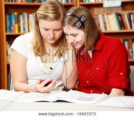 Two pretty teen girls in the school library, listening to an mp3 player.