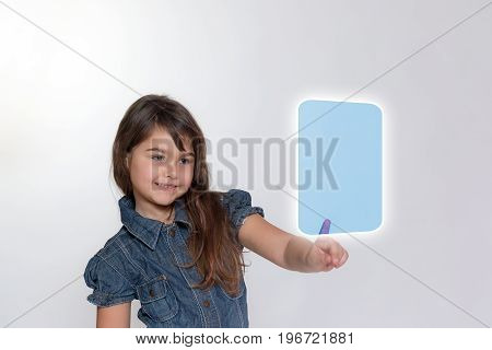 On the left side standing smiling little girl is touching a blank transparent rectangle by her index finger. All is on the light gray background.