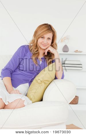Pretty Red-haired Woman Posing While Sitting On A Sofa