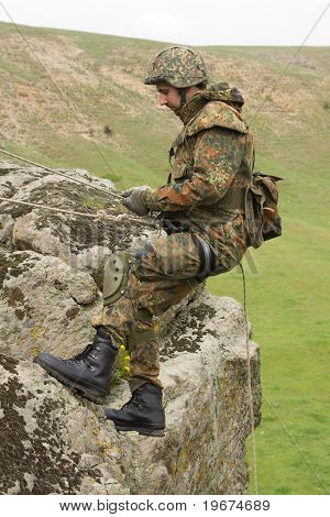 Soldier Climbing Down The Rock
