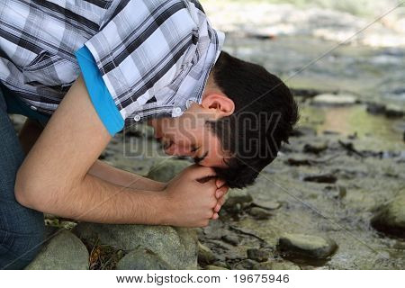 Man Praying by Creek