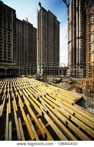 On wood planking between tall buildings under construction and cranes under a blue sky