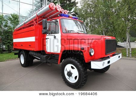 Big red fire engine with pipes and flasher on the roof at summer day
