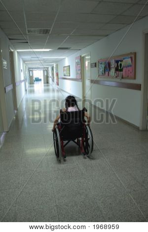 A Young girl alone on wheelchair in a