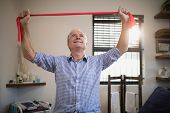 Smiling senior male patient pulling red resistance band while looking up at hospital ward poster