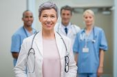 Portrait of smiling woman doctor standing in hospital with team in background. Senior female doctor  poster