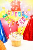 Happy birthday message on a cupcake surrounded by party balloons and hats.  poster