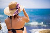 A Young Girl On A Beach With A Hat, Sun And Enjoys The Sun, On The Shoulder Drawn Sun From Sun Cream poster