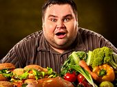 Fat man who makes choice between healthy and unhealthy food. Overweight male with hamburgers, french poster