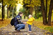 Father And His Toddler Son Walking In Autumn Park poster
