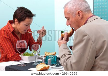 Photo of a mature married couple eating a meal in a restaurant.