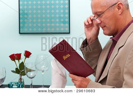 Photo of a man reading the menu in a restaurant