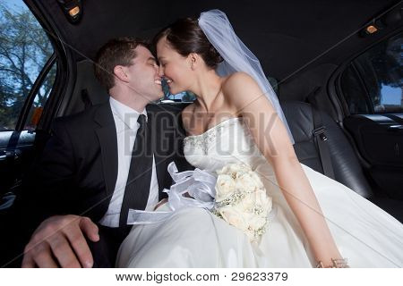 Newlywed couple kissing inside a luxurious limousine