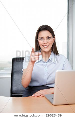 Portrait Of A Young Businesswoman Pointing At The Viewer In Her Office.