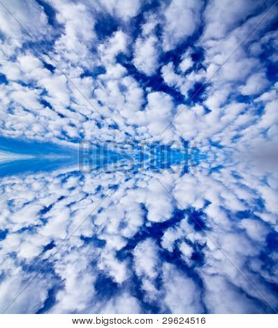Bright Blue Sky With White Clouds Mirrored On Water Surface