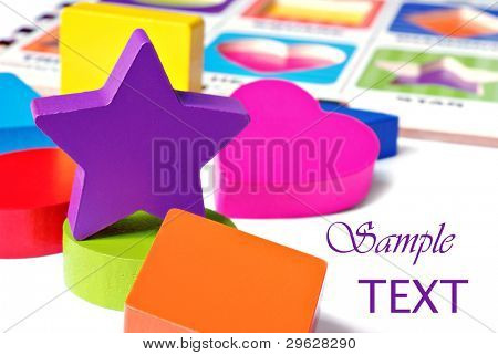 Colorful wooden geometric shaped puzzle pieces on white background with puzzle board in  background.  Macro with shallow dof.