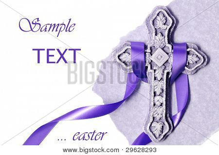 Easter background image of small ornate stone cross with purple satin ribbon and parchment paper on white background with copy space.