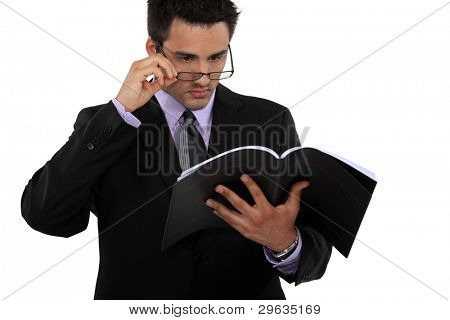 Man peering over his glasses and holding a book