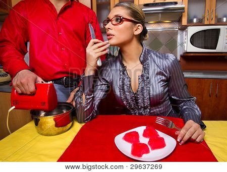 Happy young woman eating red jelly hearts and her boyfriend using hand blender on kitchen
