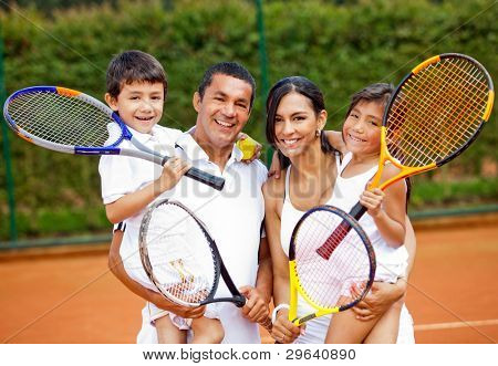 Happy family playing tennis holding rackets at the court