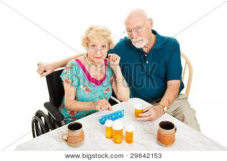 Senior couple frustrated by health issues, sitting at the table surrounded by pill bottles.  Isolated on white.