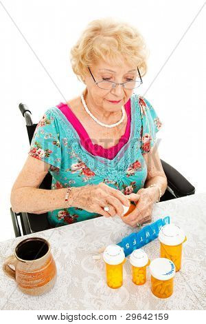 Disabled senior woman in a wheelchair, counting out her medications for the week.  White background.
