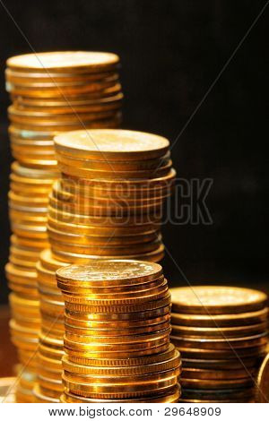 Stacks of the gold coins close up over black background
