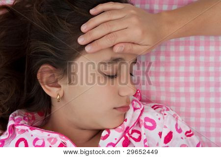 Portrait of a beautiful hispanic girl sick with fever while a hand measures her temperature