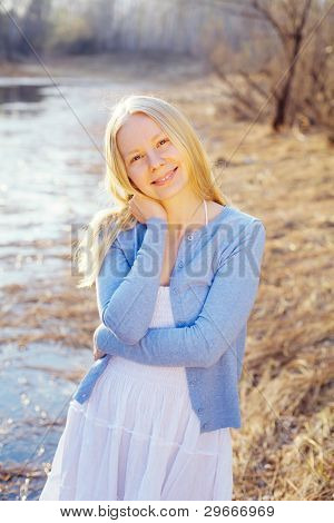 Romantic blonde young woman wearing white dress and blue jacket outdoor into autumn forest near river.