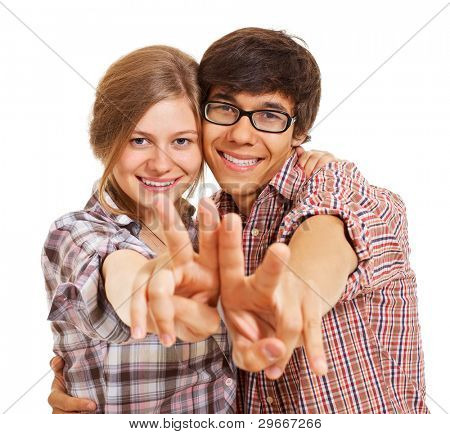 Pretty smiling girl and boy in checked shirts standing and showing victory symbol over isolated background