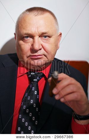 Portrait of serious businessman in black suit and red shirt with cigar
