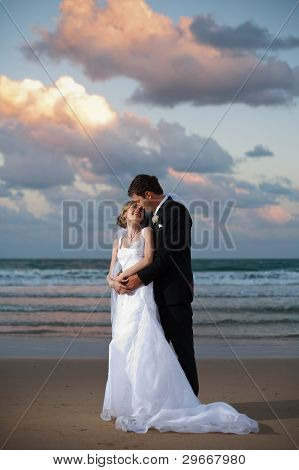 Bride And Groom Hugging On The Beach At Sunset