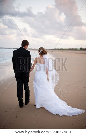 Bride And Groom Holding Hands And Walking On A Beach