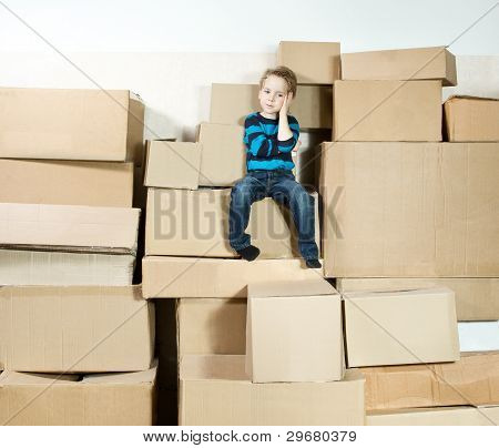Child Sitting On The Top Of Stack Packed Boxes.