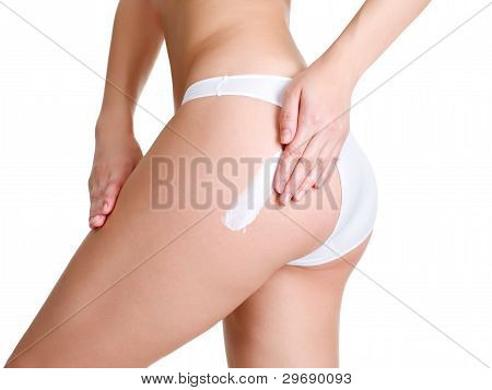 Female Applying Cosmetic Cream On Leg