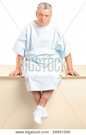 A worried senior patient sitting in a hospital after hearing a bad diagnose isolated on white background