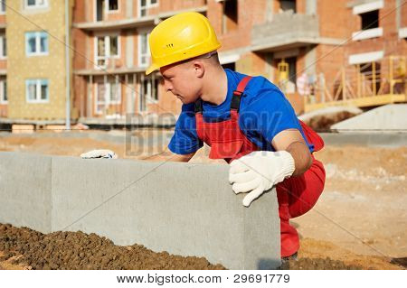 Builder worker using installing raod concrete road kerb curb at construction site